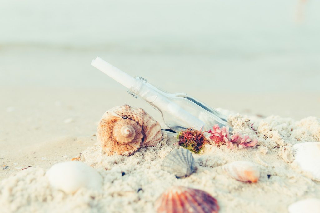 sand, seashells, message in a bottle